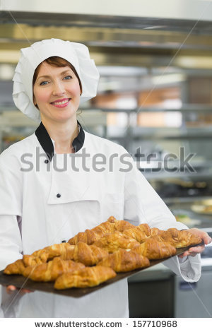 stock-photo-young-baker-presenting-croissants-on-a-baking-tray-157710968.jpg